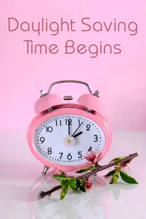 begins: Daylight savings time begins clock concept for start at Spring against a pink background, with text message.