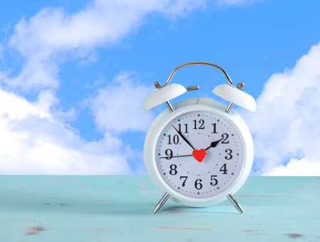 daylight savings time: Daylight savings time white clock on a vintage aqua blue wood table against a sky with clouds background.