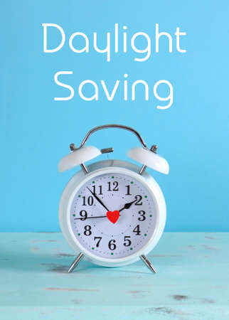 daylight savings time: Daylight savings time white clock on a vintage aqua blue wood table against a pale blue background, with sample text.