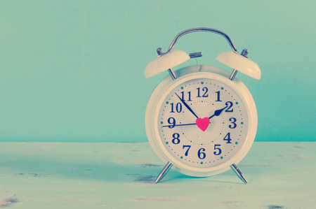Retro vintage style classic white alarm clock on vintage blue background for daylight saving or time concept. Stock Photo