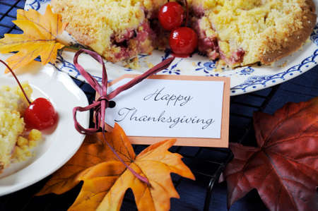 Happy Thanksgiving table setting with cherry apple crumble pie on a vintage blue plate with autumn leaves on blue tablecloth. Close up. photo