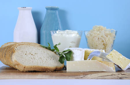 naturopath: Healthy Food Diet: Probiotic Food including sour dough bread, sauerkraut, yogurt, Parmigiano-Reggiano and Camembert cheeses on wood chopping boards against a blue background.