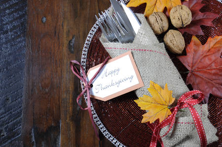 happy feast: Happy Thanksgiving dining table place setting in traditional rustic country style with hessian wrapped cutlery on rustic wood background, with copy space. Stock Photo