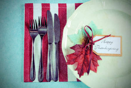 thanksgiving dinner: Retro vintage style Happy Thanksgiving dining table place setting in modern pale blue, red and white theme with vintage turkey tureen. Stock Photo