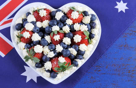 downunder: Red, white and blue theme berries with fresh whipped cream stars in white heart shape flag on rustic dark blue wood background, with Australian flag, with copy space.