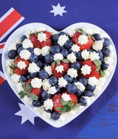 australia day: Red, white and blue theme berries with fresh whipped cream stars in white heart shape flag on rustic dark blue wood background, with Australian flag. Stock Photo
