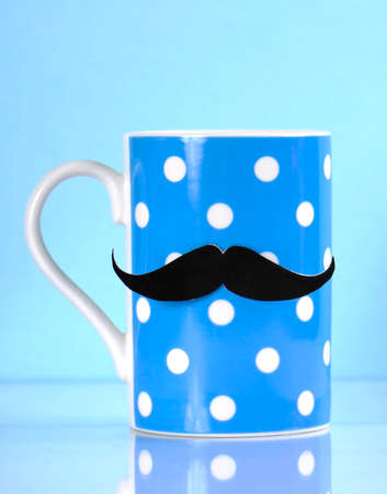 fundraising: Movember fundraising for mens health awareness charity with mustache on blue polka dot coffee mug cup on blue background.