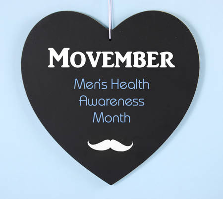 Movember fundraising for mens health awareness charity message on black heart shape blackboard on blue background.