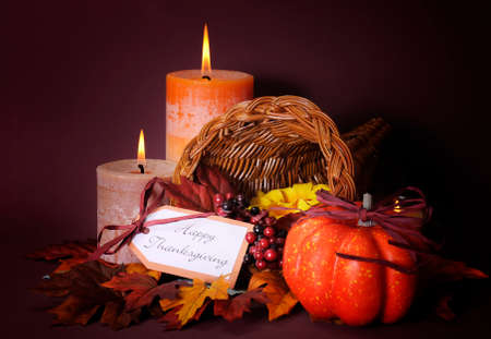 Happy Thanksgiving cornucopia wicker basket with autumn leaves, pumpkin and greeting tag on candlelit background.