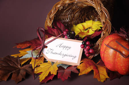 happy feast: Happy Thanksgiving cornucopia wicker basket with autumn leaves, pumpkin and greeting tag on candlelit background. Close up.