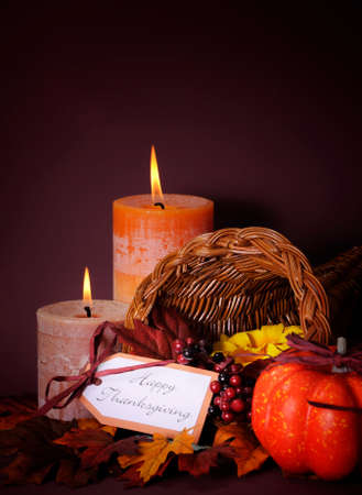 horn of plenty: Happy Thanksgiving cornucopia wicker basket with autumn leaves, pumpkin and greeting tag on candlelit background. Vertical with copy space. Stock Photo