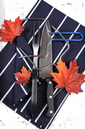 prongs: Thanksgiving roast turkey carving utensils set with dark blue stripe apron on white vintage shabby chic table top with autumn leaves. Vertical overhead.