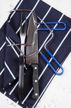 Roast turkey carving utensils set with dark blue stripe apron on white vintage shabby chic table top. photo