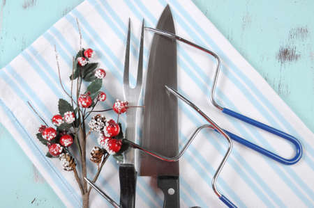prongs: Christmas roast turkey carving utensils set with pale blue and white stripe apron on vintage shabby chic table top, with berry and mistletoe decoration.