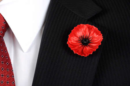 November 11, Armistice Day, Red Poppy for Lest We Forget remembrance, closeup on button hole of man with black suit, white shirt and red tie.