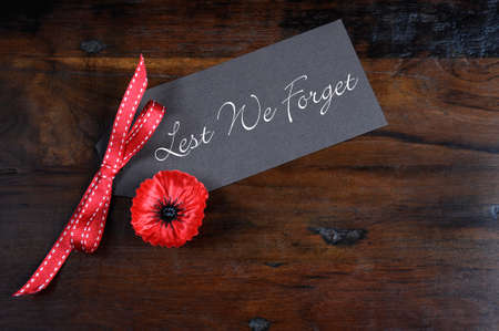 Lest We Forget, Red Flanders Poppy Lapel Pin Badge for November 11, Remembrance Day appeal, on dark recycled wood background.