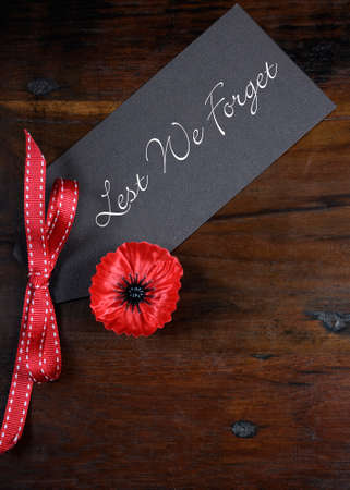 anzac: Lest We Forget, Red Flanders Poppy Lapel Pin Badge for November 11, Remembrance Day appeal, on dark recycled wood background. Vertical.