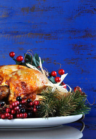 space for copy: Scrumptious roast turkey chicken on platter with festive decorations for Thanksgiving or Christmas lunch, against dark blue rustic wood background. Vertical with copy space.