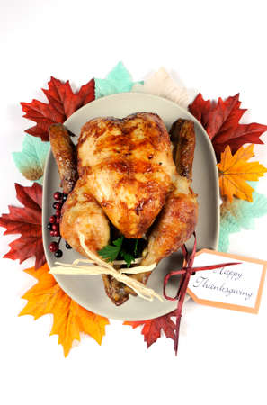 Scrumptious roast turkey chicken on platter with festive decorations for Thanksgiving lunch with autumn Fall leaves on white table. Vertical. photo