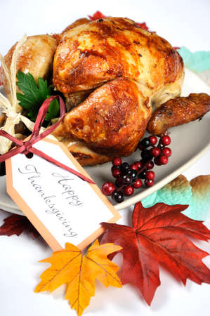Scrumptious roast turkey chicken on platter with festive decorations for Thanksgiving lunch with autumn Fall leaves on white table. Closeup. photo