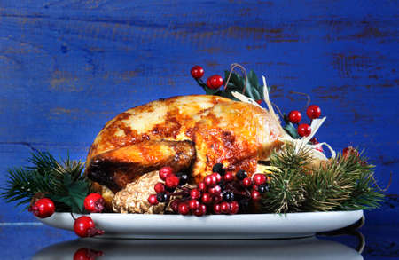 Scrumptious roast turkey chicken on platter with festive decorations for Thanksgiving or Christmas lunch, against dark blue rustic wood background. photo