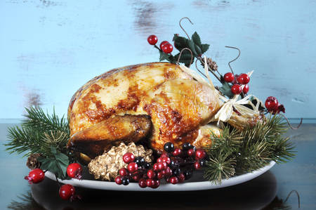 Scrumptious roast turkey chicken on platter with festive decorations for Thanksgiving or Christmas lunch, against shabby chic aqua blue rustic wood background. photo