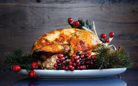 Scrumptious roast turkey chicken on platter with festive decorations for Thanksgiving or Christmas lunch, against dark recycled wood background.