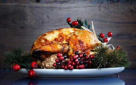 aves de corral: Riquísimo pollo pavo asado en un plato con adornos festivos para el almuerzo de Acción de Gracias o Navidad, contra el fondo de madera oscura reciclado. Foto de archivo