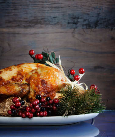 Scrumptious roast turkey chicken on platter with festive decorations for Thanksgiving or Christmas lunch, against dark recycled wood background. Vertical with copy space.