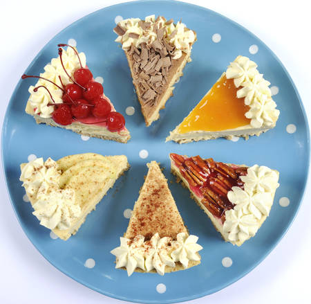 Thanksgiving apple, pecan, cherry, caramel, pumpkin spice and chocolate cream cheesecake pie, on blue polka dot platter against a white table. photo