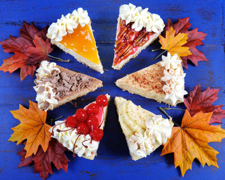 cream pie: Thanksgiving apple, pecan, cherry, caramel, pumpkin spice and chocolate cream cheesecake pie on dark blue vintage wood background, with autumn Fall leaves. Stock Photo