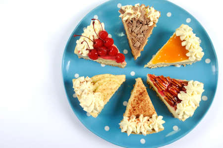 Thanksgiving apple, pecan, cherry, caramel, pumpkin spice and chocolate cream cheesecake pie, on blue polka dot platter against a white table, with copy space. photo