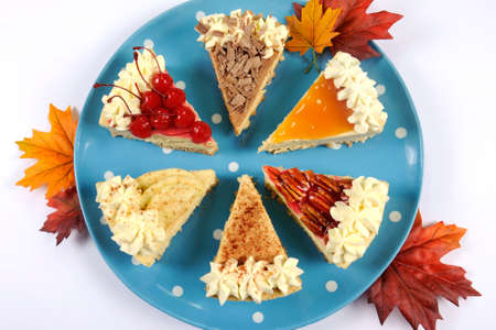 Thanksgiving apple, pecan, cherry, caramel, pumpkin spice and chocolate cream cheesecake pie, on blue polka dot platter against a white table, with autumn fall leaves. photo