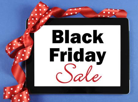 long weekend: Nero Messaggio di vendita Venerd� su tablet computer nero con nastro rosso su sfondo blu. Archivio Fotografico