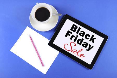 long weekend: Nero Messaggio di vendita Venerd� su tablet computer nero con una tazza di caff� su sfondo blu. Archivio Fotografico