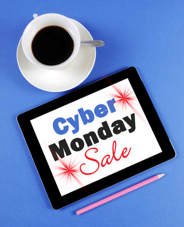 long weekend: Cyber Monday Sale message on black computer tablet device with cup of coffee on blue background.