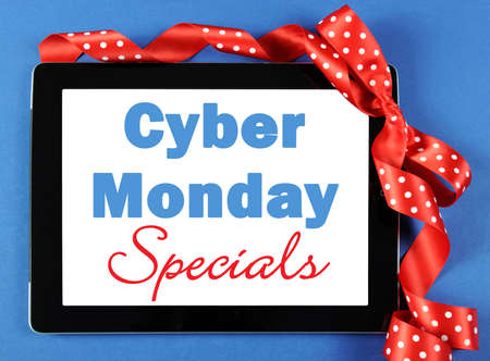 long weekend: Cyber Monday Specials sale shopping sign on black computer tablet device on blue background with red polka dot ribbon.