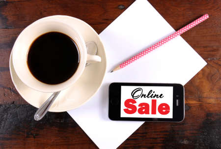 Online Sale message on phone device with cup of coffee, pencil and paper for Cyber Monday Sales photo