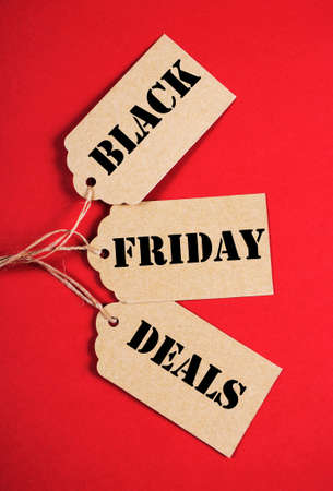 long weekend: Black Friday Sale message sign on brown paper sale tags on red background. Vertical. Stock Photo