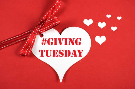 Giving Tuesday philanthropy day after Black Friday shopping message sign white heart on red background and sample text. Stock Photo