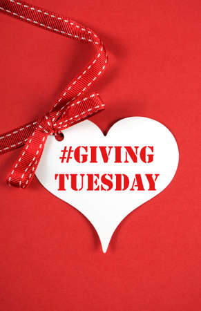 philanthropy: Giving Tuesday philanthropy day after Black Friday shopping message sign with white heart on red background and sample text. Vertical. Stock Photo
