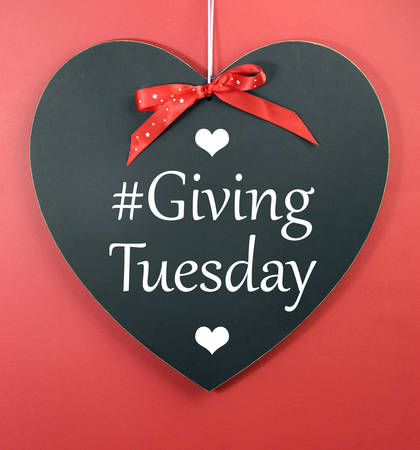 Giving Tuesday message greeting on black heart shape blackboard against a red background. Stock Photo