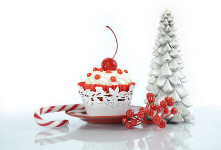 red velvet cupcake: Happy Christmas red velvet cupcake with cherry and tree on reflective white background.