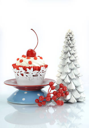 red velvet cupcake: Happy Christmas red velvet cupcake with cherry and tree on reflective white background. Vertical.