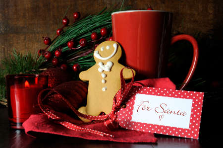 Christmas Eve setting with gingerbread and red cup of coffee for Santa in traditional dark wood rustic setting. photo