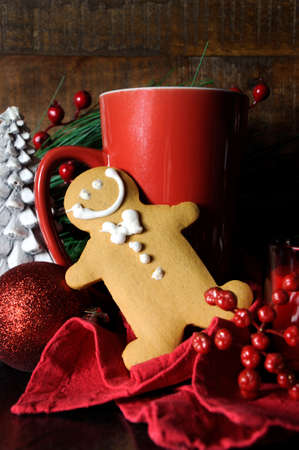 Christmas Eve setting with gingerbread and red cup of coffee for Santa in traditional dark wood rustic setting. Vertical. photo