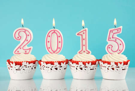Happy New Year for 2015 red velvet cupcakes in red and white theme with lit candles and pale blue and white background, photo