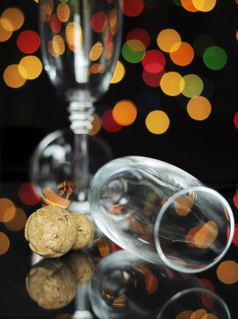 new year eve: Happy New Year Eve party with champagne glasses and cork on reflective table against bright color festive bokeh lights. Vertical. Stock Photo