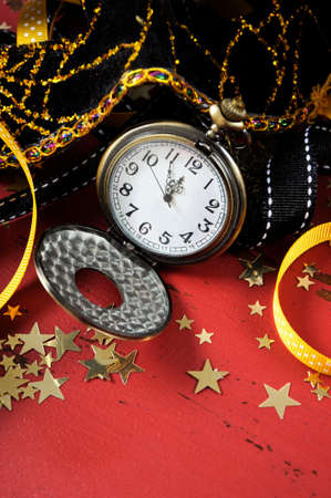 fib: Happy New Year pocket fob watch with five to midnight time and decorations on red rustic distressed vintage wood. Vertical.