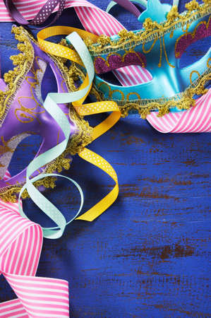 masquerade masks: Happy New Year background with pink, purple and blue masquerade party masks and decorations on dark blue rustic distressed vintage wood. Vertical closeup. Stock Photo